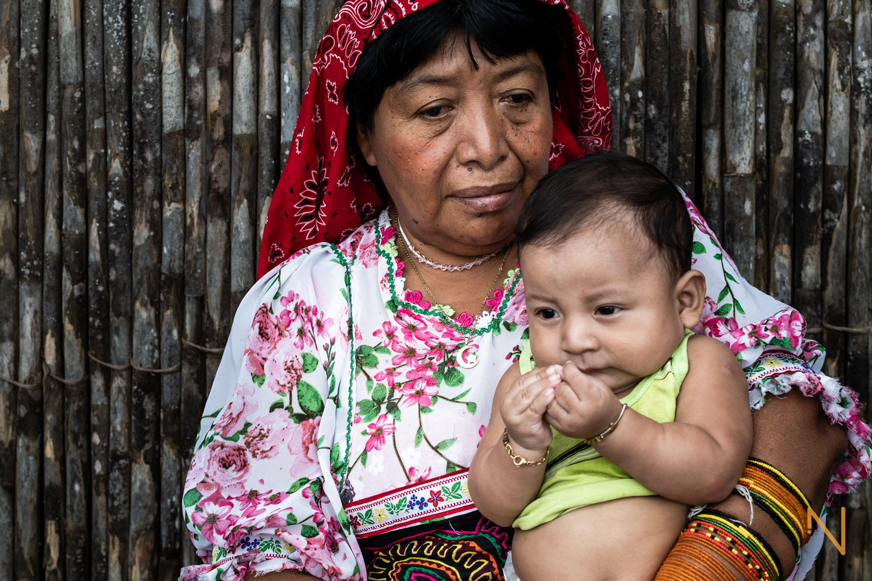 Portrait of Edita Lopez holding her grandson.