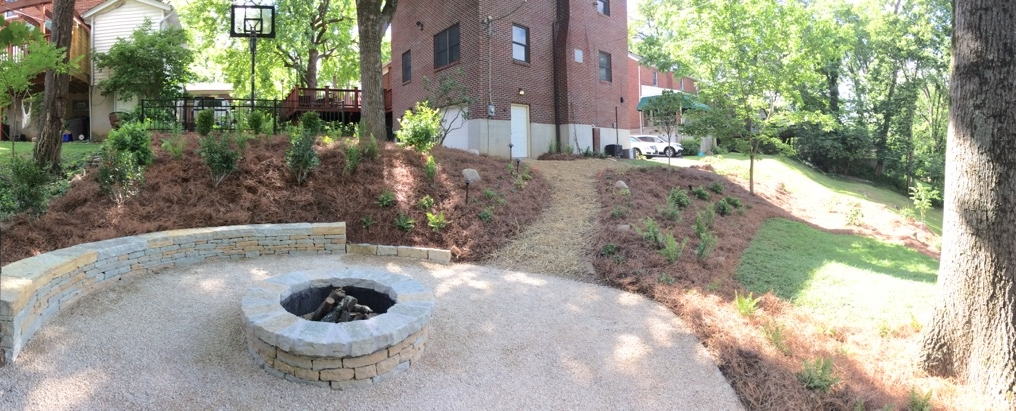 The crushed stone patio and natural stone fire pit will have a backdrop of native ferns and shrubs