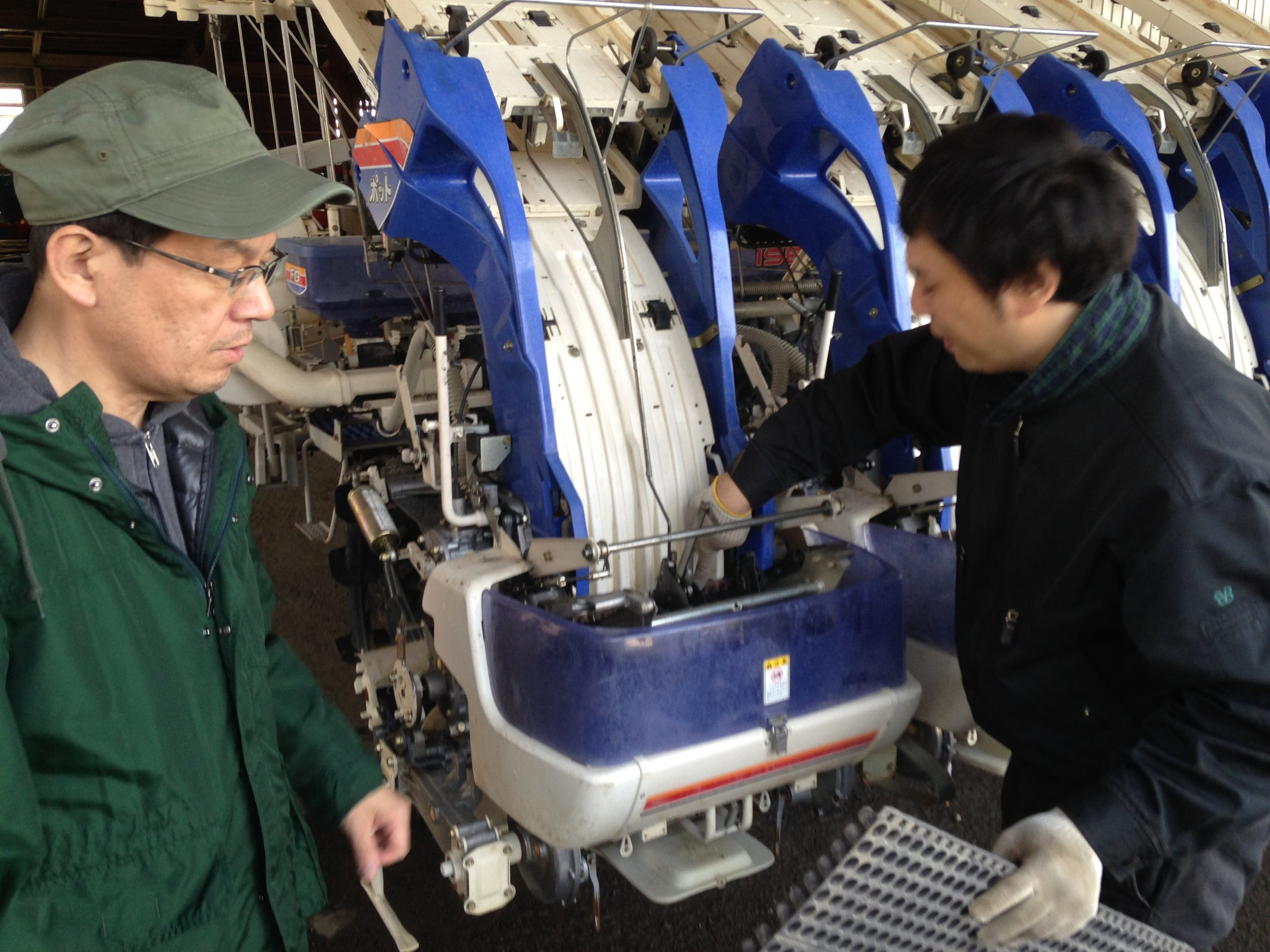 "Mr. Ashihara, a techinician for JA Hokkaido / Hokkuren in Iwamizawa shows the mechanism of a ""pot-type"" rice transplanter to me and Takehiro Ono."