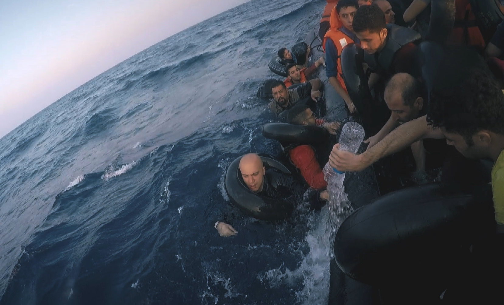 Hassan Akkad, one of the filmmakers and subjects of Exodus, on an imperiled raft with other refugees trying to cross the Mediterranean. (Image courtesy FRONTLINE.)