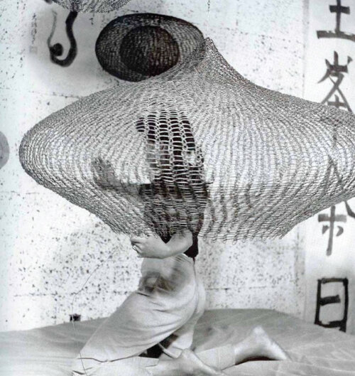 "Cunningham, Imogen. ""Untitled (Ruth Asawa on bed kneeling inside looped wire sculpture), 1957"". Gelatin silver print. Gift of Ruth Asawa and Albert Lanier. Achenbach Foundation. 2006. 114.4. San Francisco."