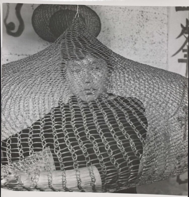 "Cunningham, Imogen. ""Untitled (Ruth Asawa on bed looking out of looped-wire sculpture), 1957."" Gelatin silver print. Gift of Ruth Asawa and Albert Lanier. Achenbach Foundation. 2006. 114.11. San Francisco."