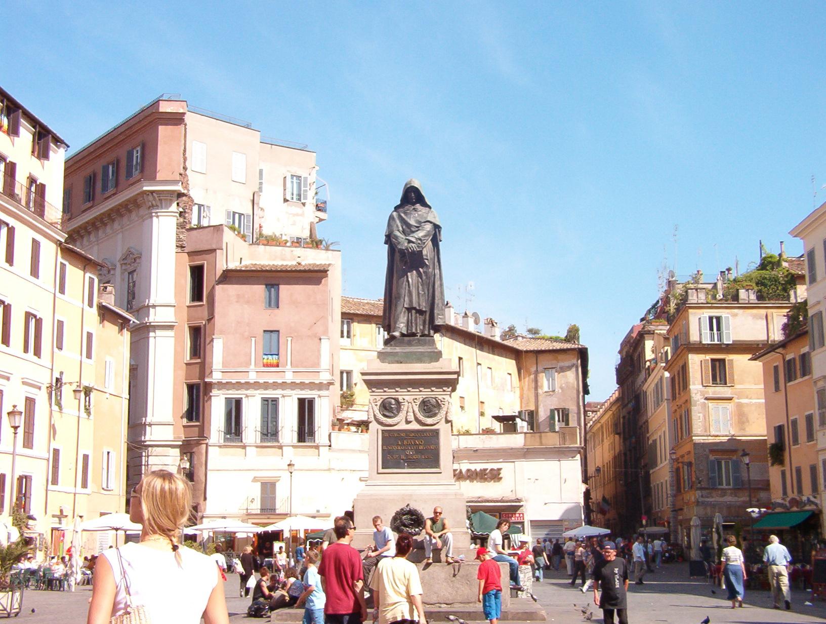 """Giordano Bruno (1548-1600) - Bruno, sonsuz evren görüşünü benimsemesi ve dünyadan başka gezegenlerin de olduğu iddiasını bıkmadan dile getirmesi nedeniyle Roma Engizisyon Mahkemesi tarafından Roma'daki Campo de' Fiori meydanınında diri diri yakıldı. Bruno, ölüm kararını kendine bildiren yargıca """"Ölümü bildirirken siz benden daha çok korkuyorsunuz."""" der.  Görsel bugünkü Campo de' Fiori meydanı ve meydandaki Giordano Bruno heykeli."""