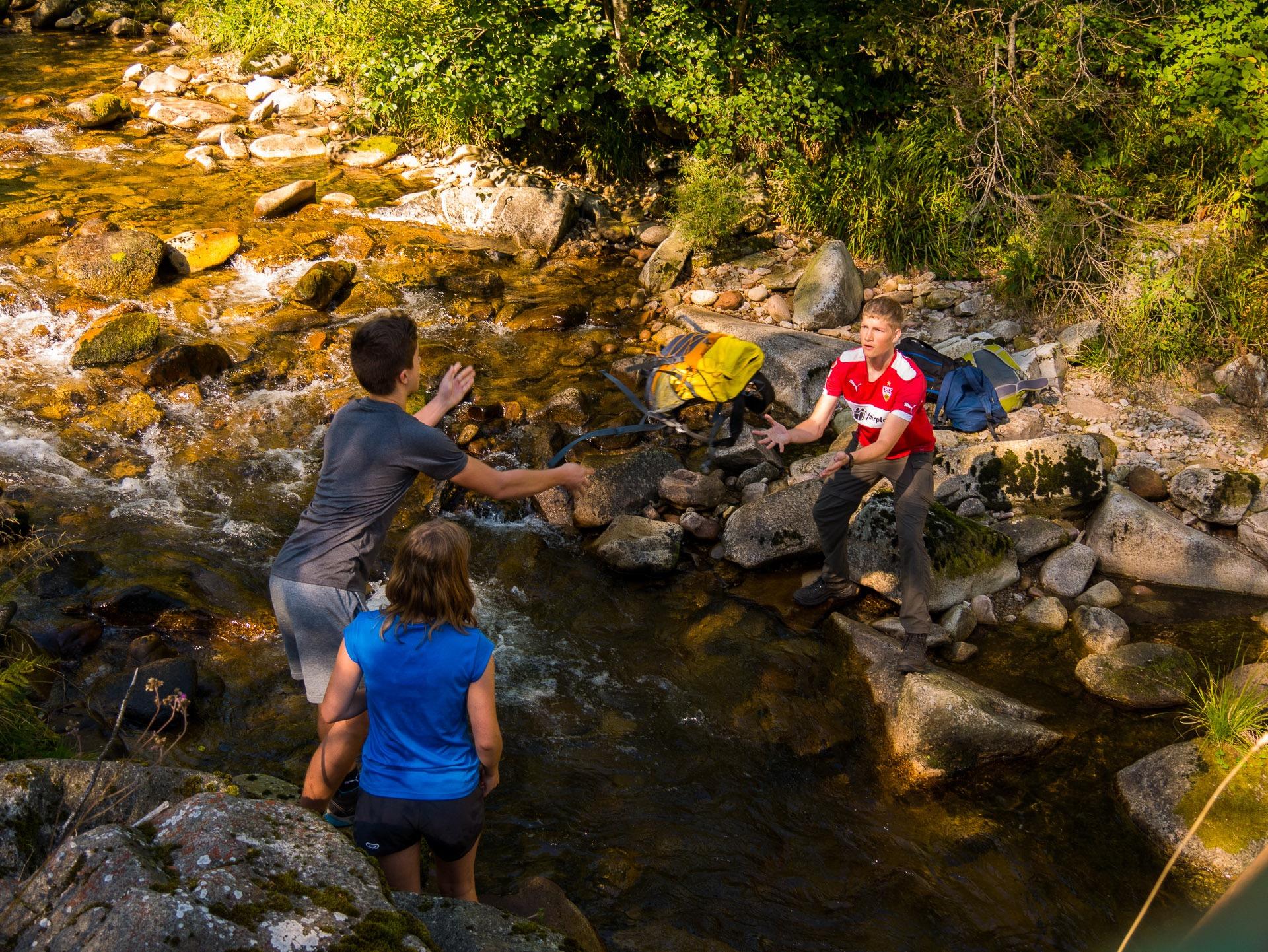 Bei der Fluss Challenge müssen die Rucksäcke über das Wasser transportiert werden, ohne dass die nebenliegende Brücke benutzt werden darf.