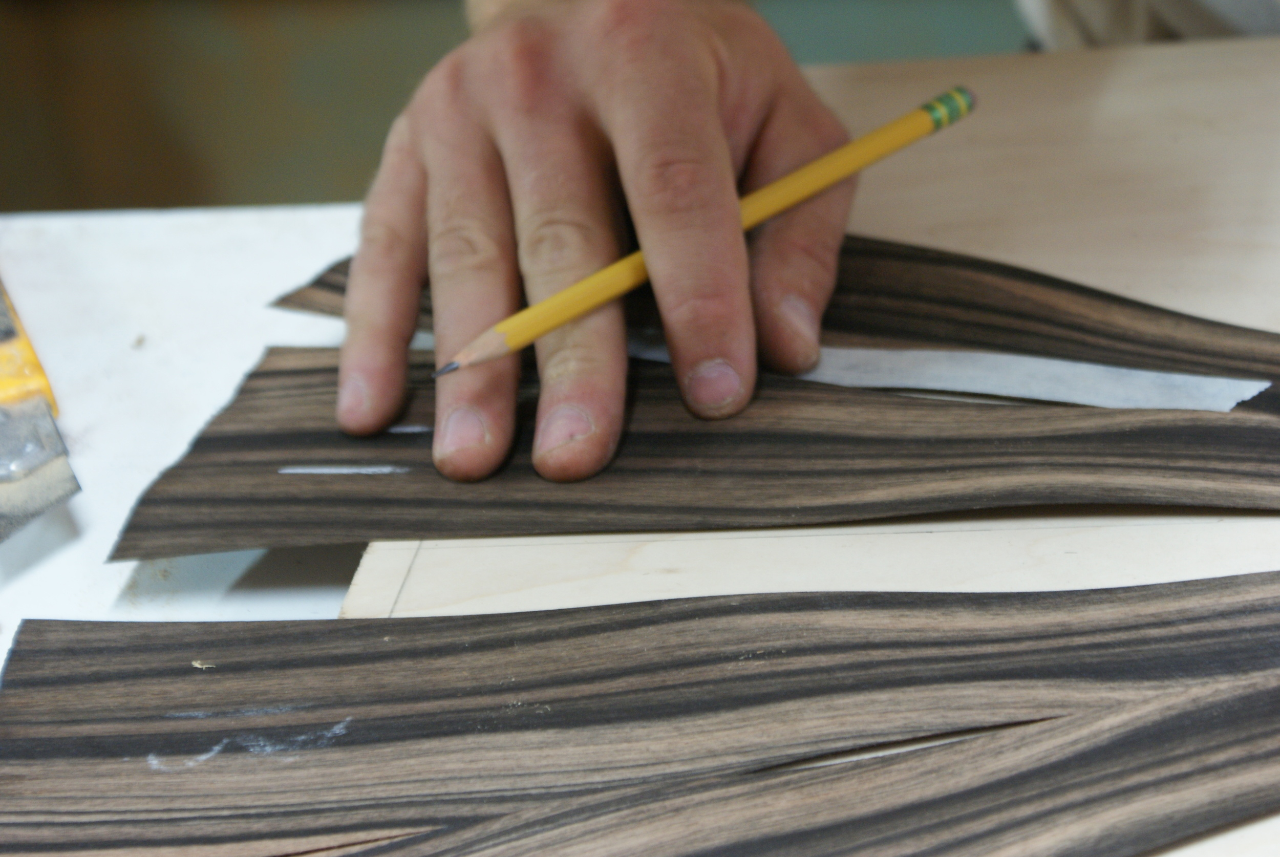 Sequenced veneer pieces are matched to the pattern drawn on the wood core.