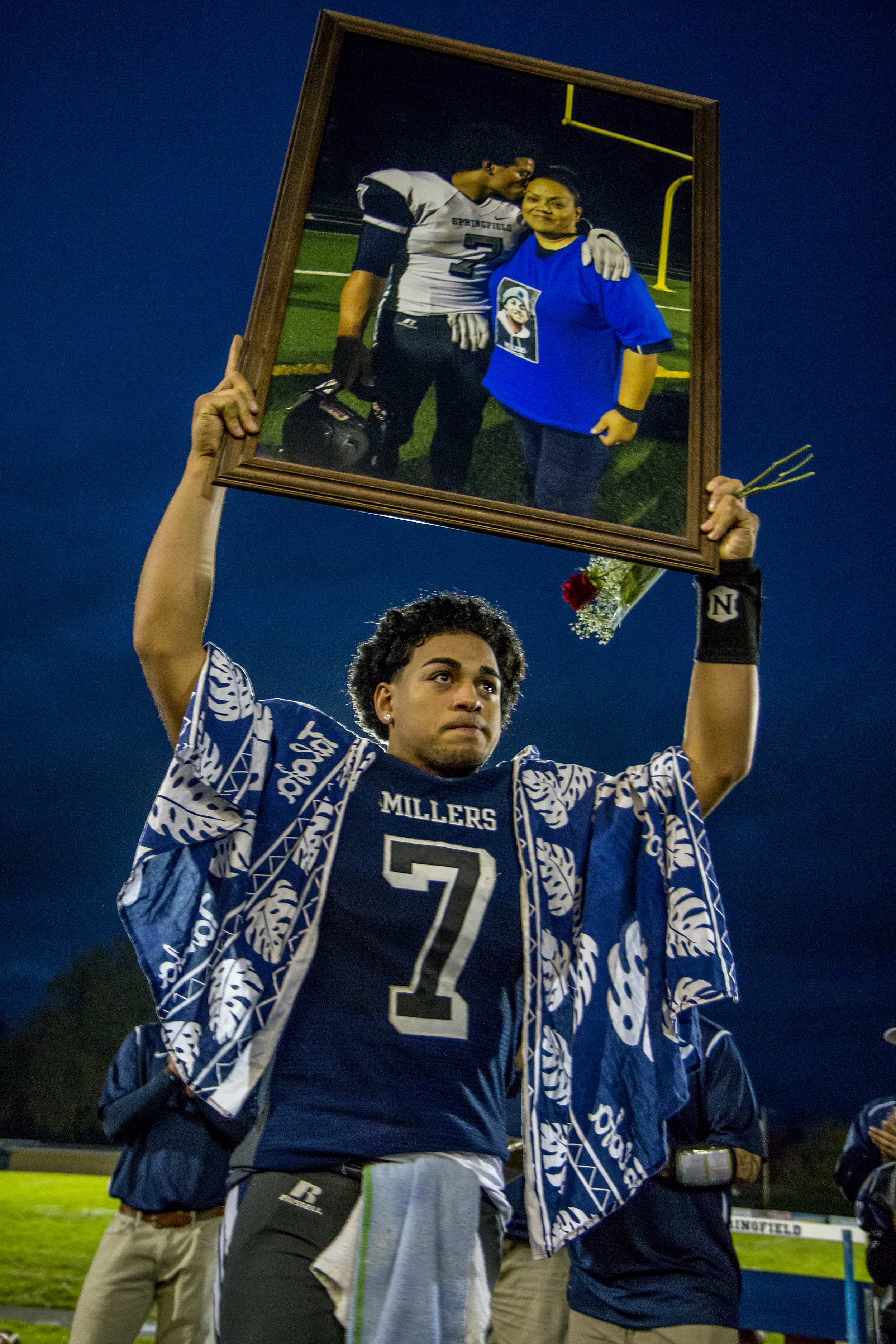 """Nick Ah Sam holds up a picture of his mother Margie at a football game at Springfield High School. His mother past away just days before the game. Within the first few minutes of the game, Ah Sam would take off on a long run to make a touchdown, a finger pointed to the sky in dedication to his mother. """"Football is just part of your life, life happens fast,"""" said the Millers coach to his assembled team after the game."""