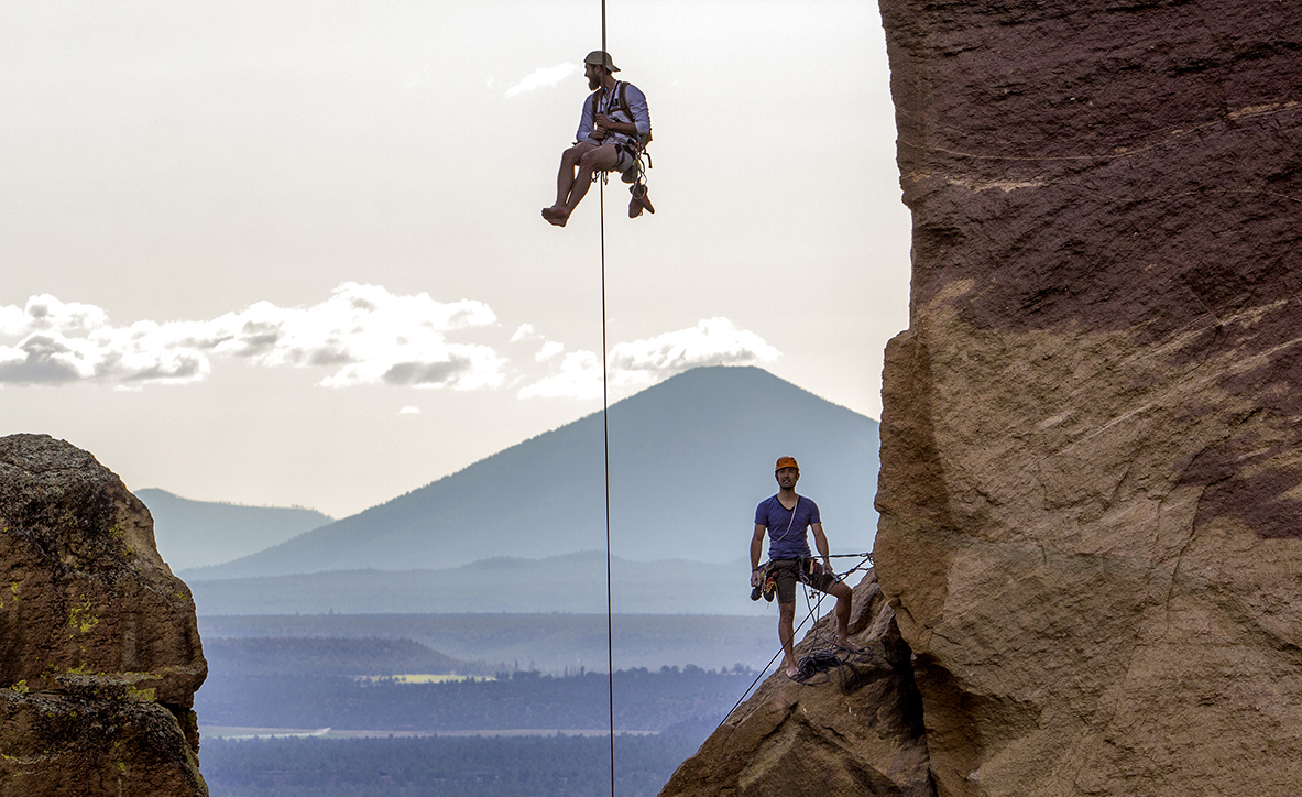 "A rock climber descends down from the rock known as ""Monkey Face"" as another climbers looks on at Smith Rock State Park. Monkey Face is a 350 foot pillar, that resembles a monkey from the correct angle. The pillar contains several of the most difficult climbs in the world, including ""just do it,"" and the ""east face"" crack. The ""just do it"" route is also the first 5.14c rated climb in the United States, an elite level grade in rock climbing."