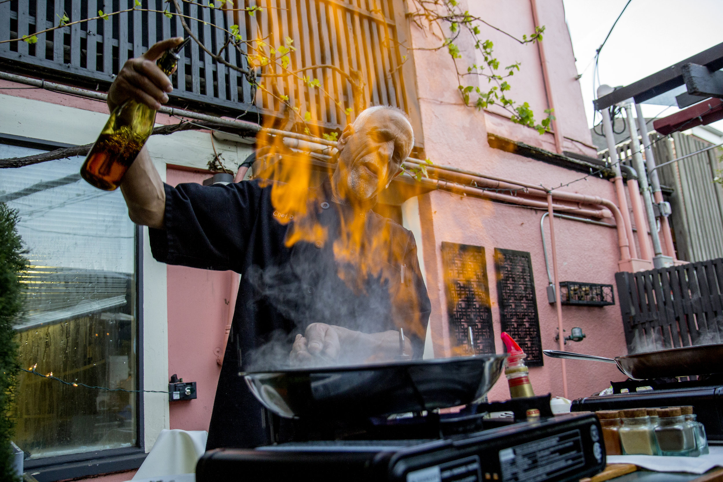 "Flames roar up over the face of head chef and owner of Café Soriah, Ibrahim Hamide, as he prepares steak diane for his customers on the back patio of Café Soriah. Hamide was born in Bethlehem in 1950 and came to Eugene to attend the University of Oregon in 1969. He quickly fell in love with the Eugene community after noticing people smiled at him, that smiling captured his heart. After 9/11, Hamide became ""the defacto spokesperson for Palestinians"" in the Eugene community."
