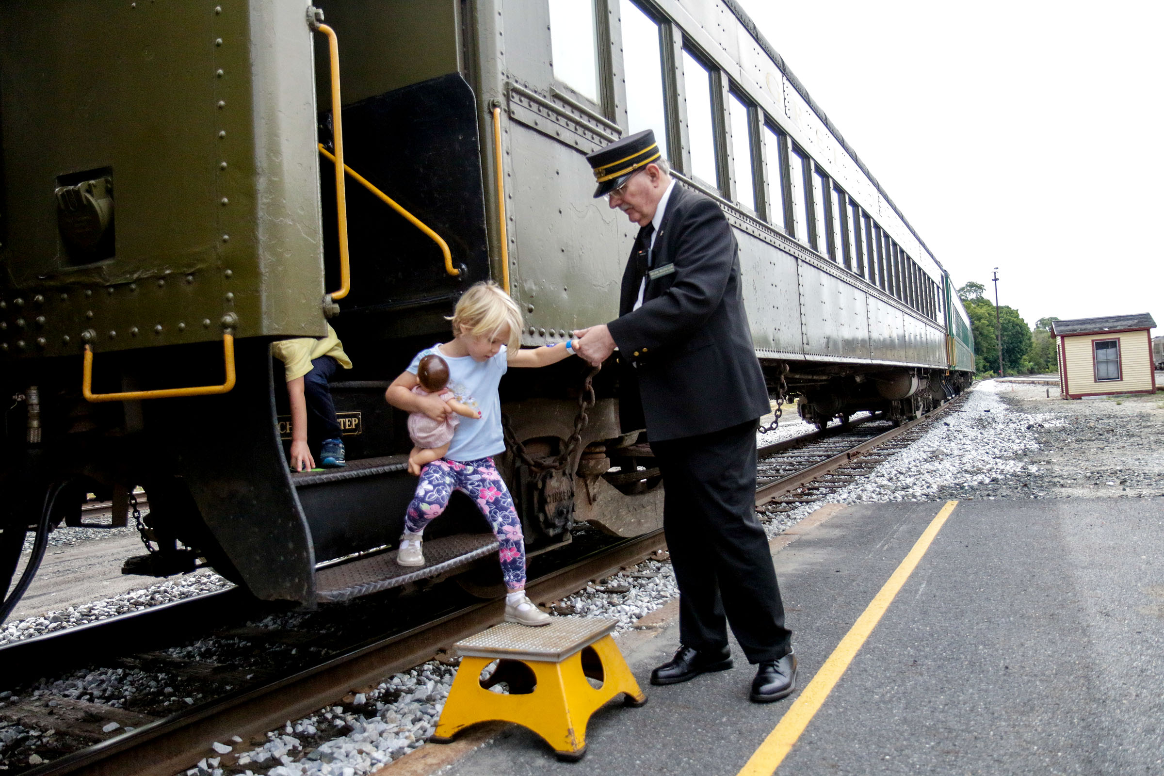 Brian McGregor, the passenger representative of Green Mountain Railroad, helps Nicole Piasecki, 3, of Hanover, N.H., off the train at the end of her 40 minute train ride at Glory Days of the Railroad in White River Junction, Vt., on Saturday, Sept. 8, 2018.