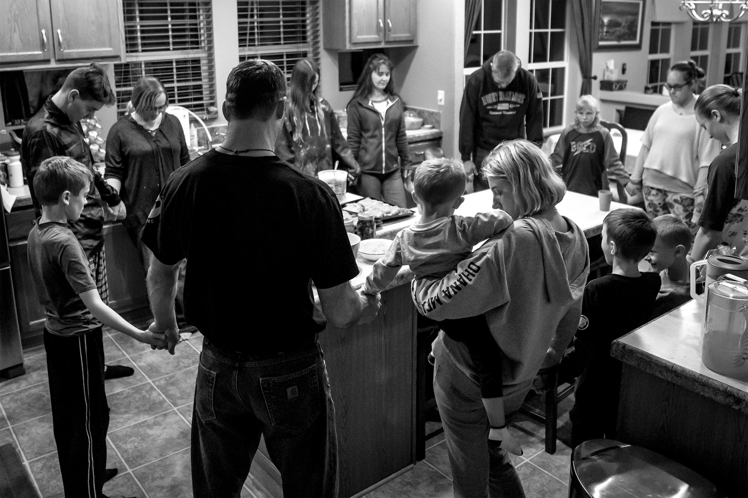 Members of the Pfeil and Mitchell family with Ukrainian orphans staying with the families through the Host Ukraine Orphan Initiative come together for a prayer before dinner on Wednesday, Jan. 9, 2019. The Pfeil family have six kids of their own, and are trying to adopt five Ukrainian orphans.