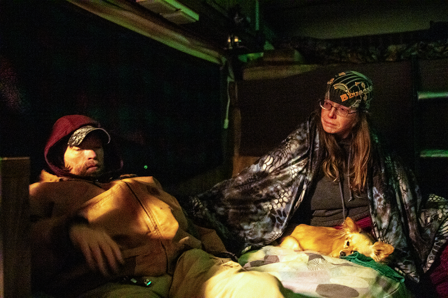 """Andrea Elliot reaches out to her """"street son"""" Jeff Stone during the evening at their mobile home on Wednesday, Jan. 23, 2019. Quarters in the home are tight, with one bed on the ground floor, another bed up top behind them, a table and chair opposite the bed and a small kitchen with stove and sink at the back."""