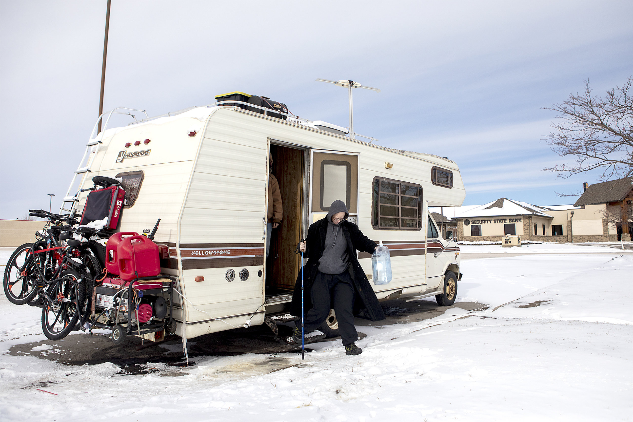 Andrea and Jeff exit their mobile home for a trip to Flying J's to get water. The family hopes to be able to travel from place to place after their home is repaired.