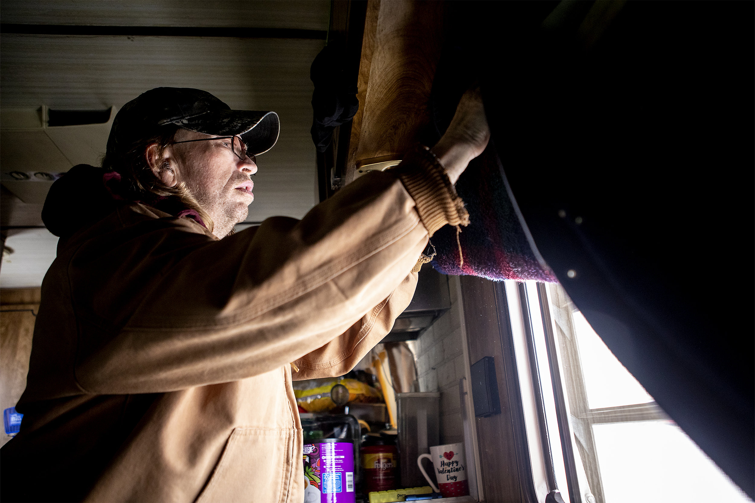 Jeff lifts the curtains of their home. During the recent cold that hit Gillette they ended up with ice on their windows and inch thick. The family relies one a heater and propane tanks to keep them and the mobile home warm during the winter.