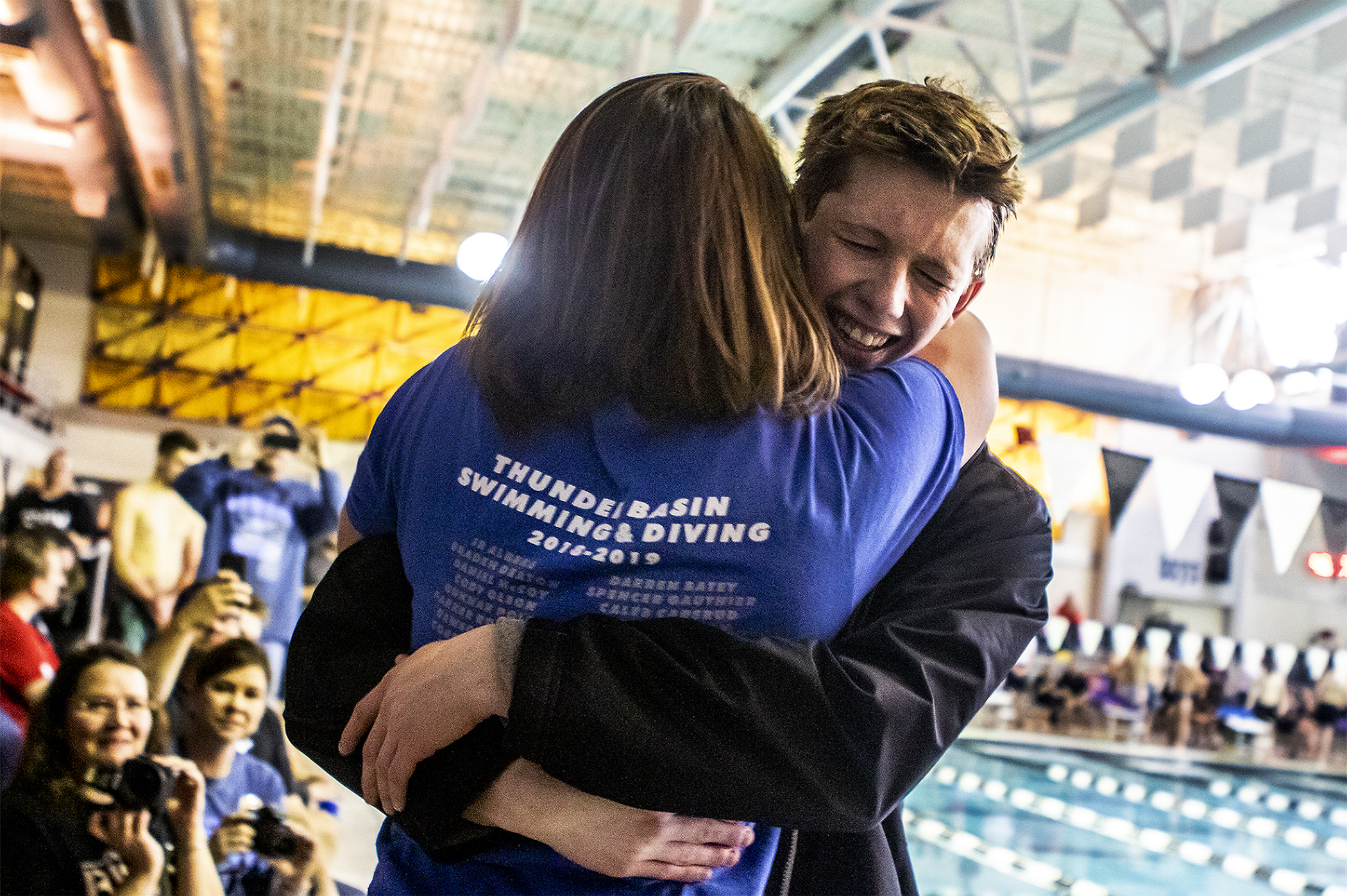 The Bolts' JR Albers hugs Bolts Swimming Coach Jade Moser as he accepts his gold medal for the boys 500 yard freestyle at the Campbell County Aquatic Center during the 4A Swim and Dive Championships on Friday, Feb. 15, 2019.