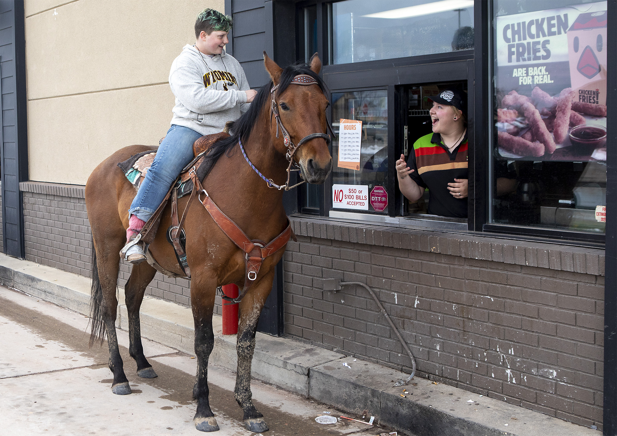 Kristie Laatsch reacts as Dana Blaszkowski, 17, rides her 5-year-old horse Ike up to the Burger King drive-thru window on Thursday afternoon. Blaszkowski decided to take a more rural method of transportation from her home in Rozet to class at Thunder Basin High School. After an unsuccessful attempt to order from the McDonald's drive-thru earlier, Blaszkowski found success at Burger King and got Ike water and some applesauce for being good. While Ike decided the applesauce wasn't for him, he did enjoy some of the grass on the side of the road.