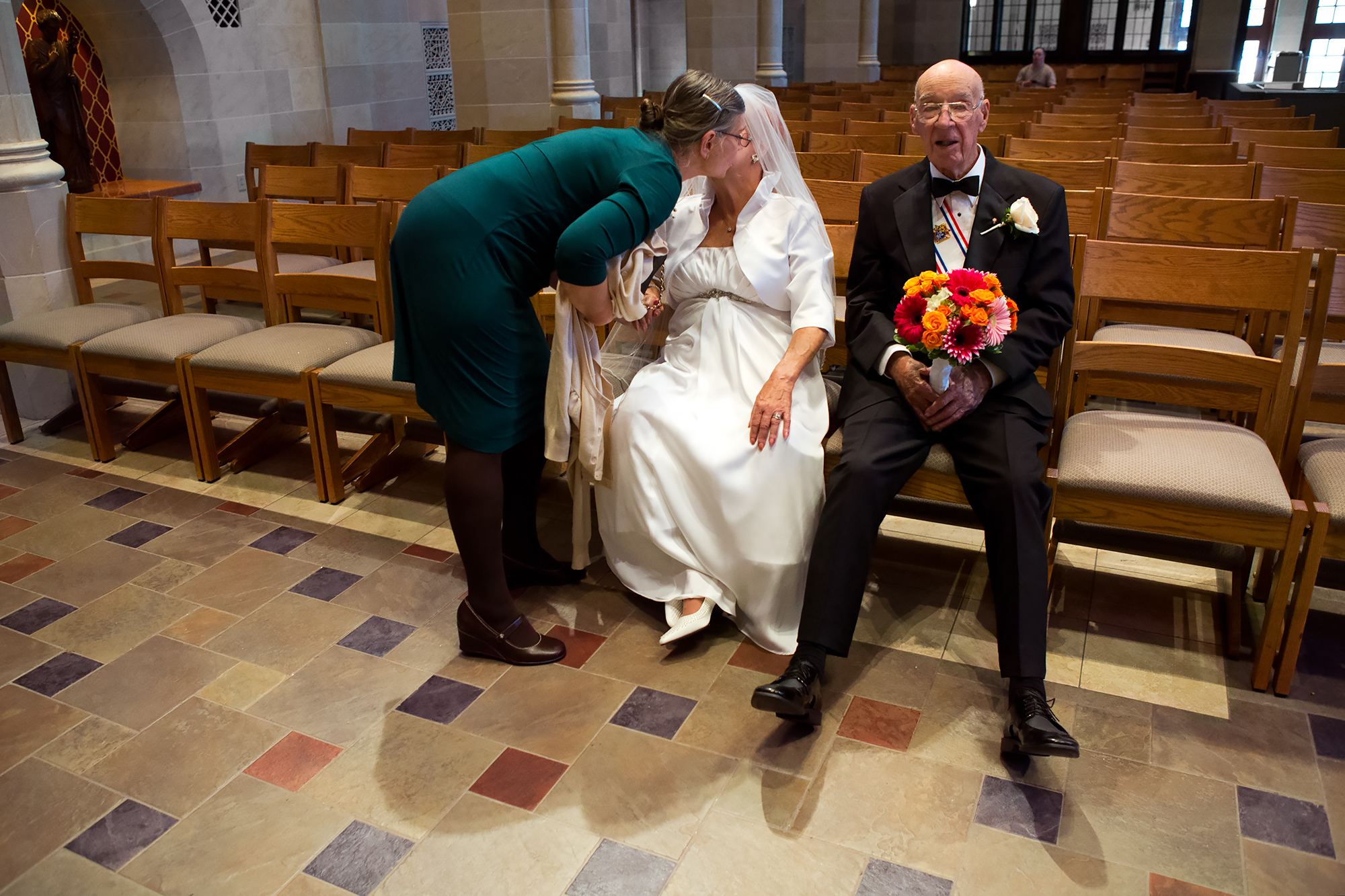Frank holds Joyce's bouquet as her sister-in-law, Ellie Kleber, congratulates her after the wedding. After a busy morning, Frank admits he is beginning to feel worn out.