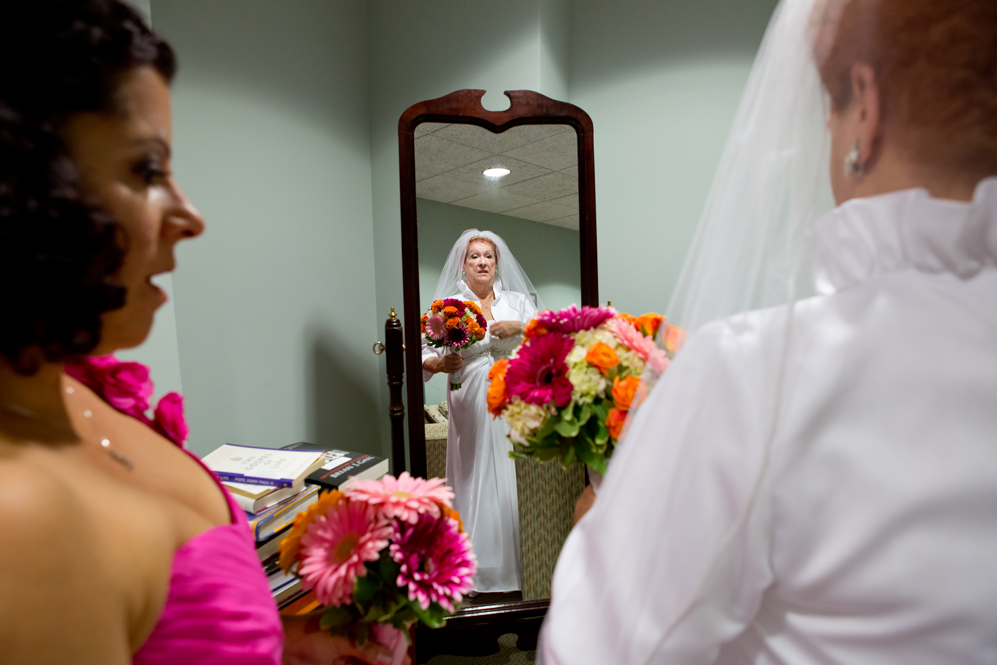Bridesmaid Pam Devos helps Joyce adjust her gown before the wedding ceremony at Sacred Heart Cathedral.