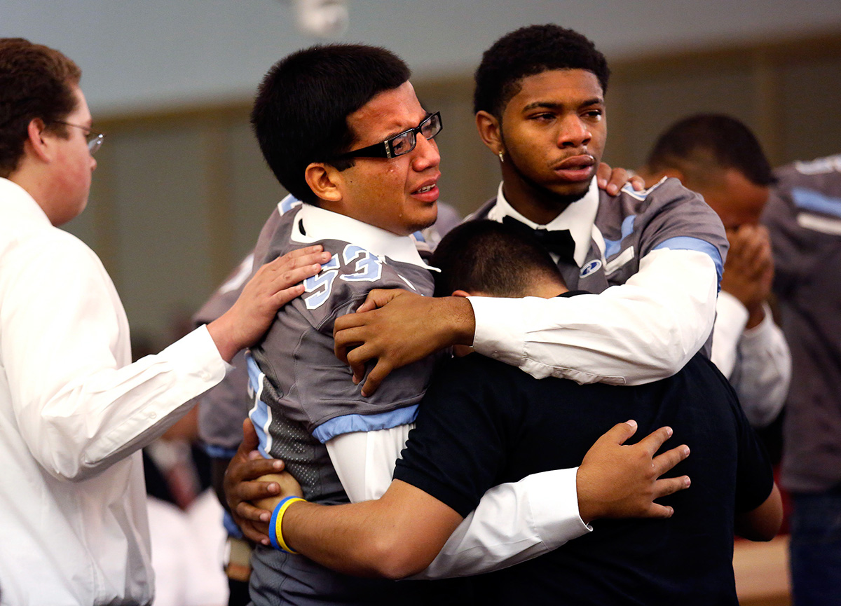 Javier Medina, 17, left, hugs his fellow Rebels teammates during the funeral for South High School's football coach John Wren at The Church of Jesus Christ of Latter-Day Saints in Bakersfield, Calif. John Wren, 44, who was considered both a father figure and mentor to the team, died unexpectedly in his sleep a week prior.