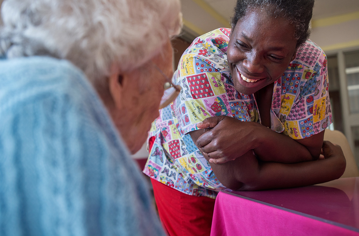Ruby visits with a resident at The Carrington, a nursing home facility where she works as a certified nursing assistant taking care of the elderly.