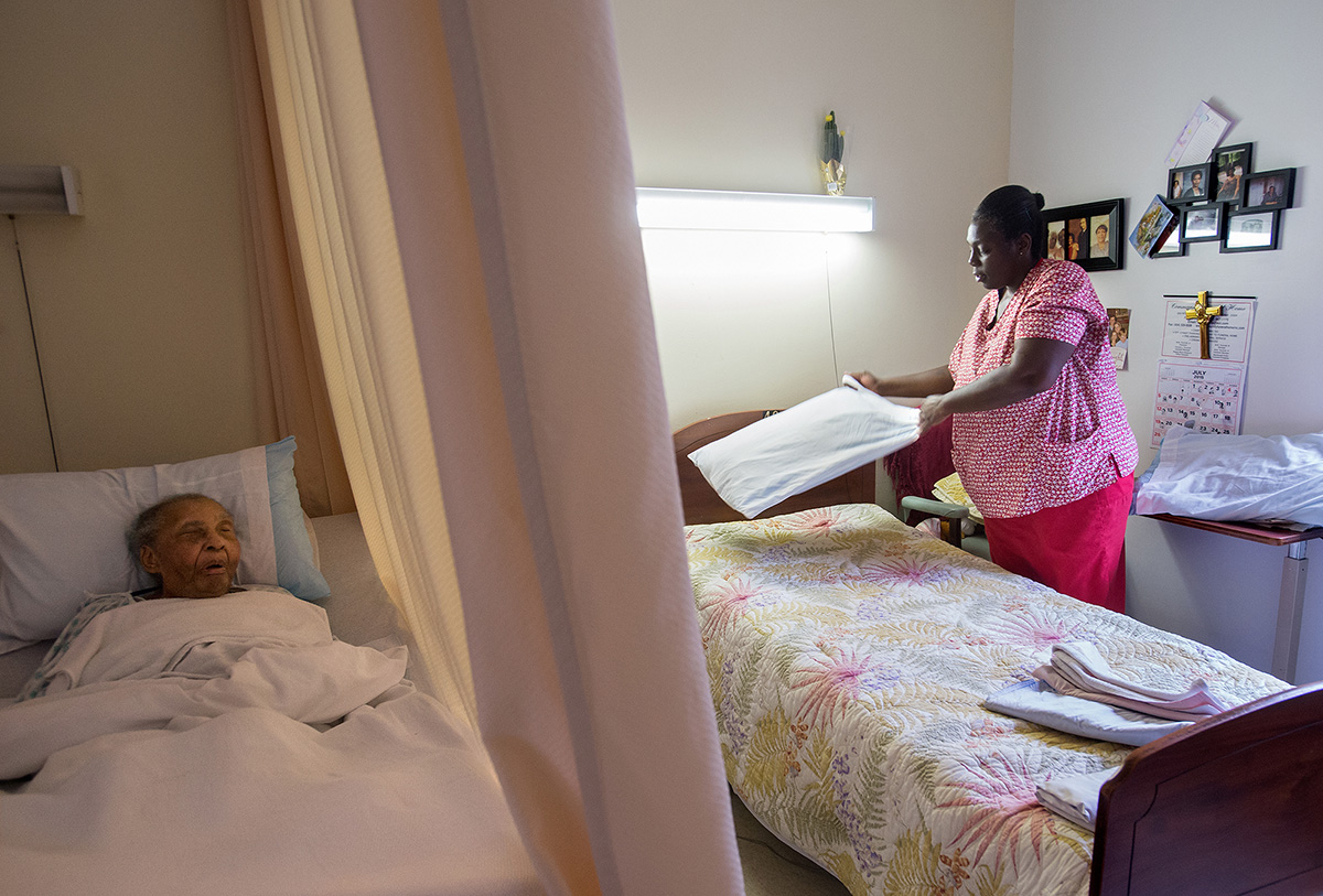 Ruby changes bed sheets during her morning rounds at The Carrington, where she is responsible for feeding, bathing and caring for the elderly in the facility.