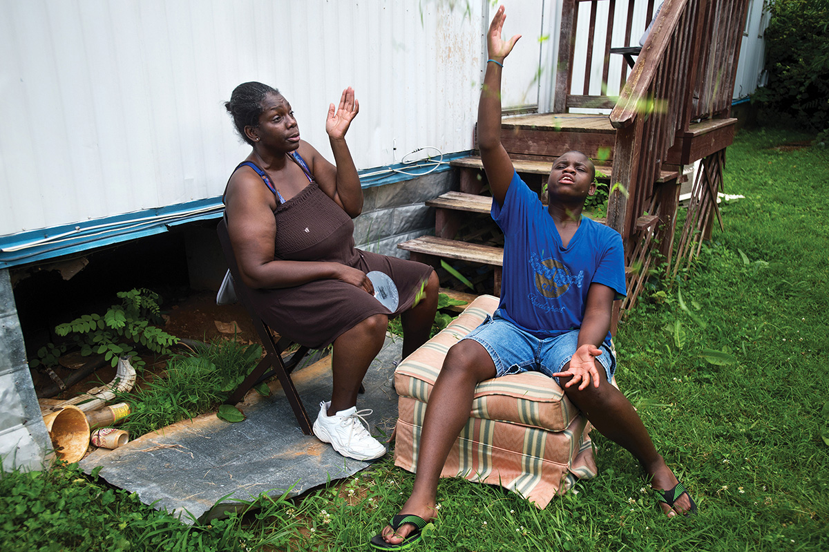 """Cortez tosses grass in the air while sitting in the yard with his mother. Ruby and her son spent the evening outdoors as temperatures rose above 90 degrees inside their home, after they lost their air conditioning because she couldn't afford to pay her bill. """"Cortez deserves better than this,""""said Ruby, who took the day off work to try to find assistance to pay her overdue electric bill."""