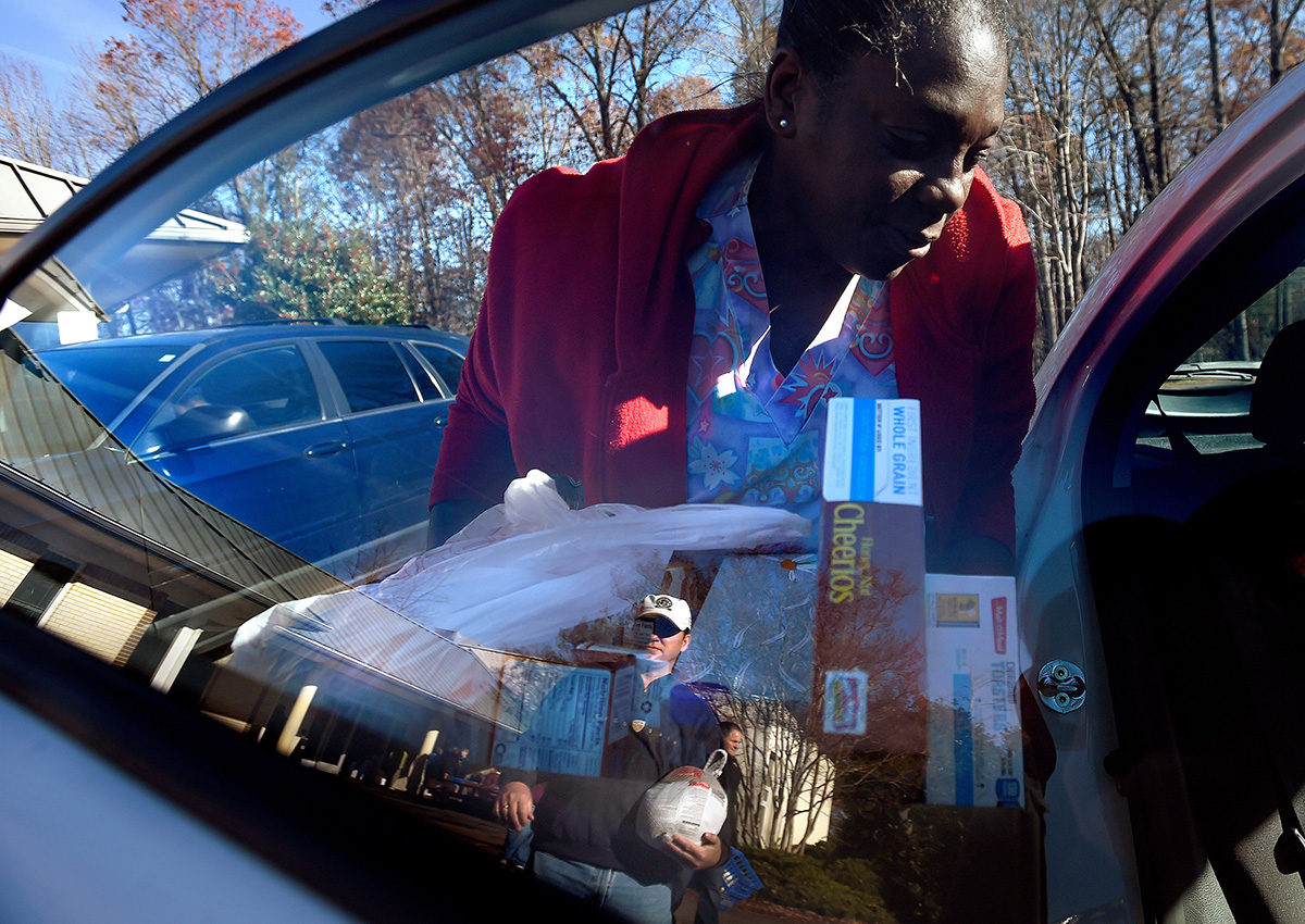 """Ruby loads donated food from Horizon Behavioral Health into a friends car for Thanksgiving at St. Thomas More Church. """"I paid my rent but we didn't have money to buy groceries,""""she said. Although her annual income as a certified nursing assistant is about $8,000 over the federal poverty threshold for a two-person household, she still struggles paycheck to paycheck."""