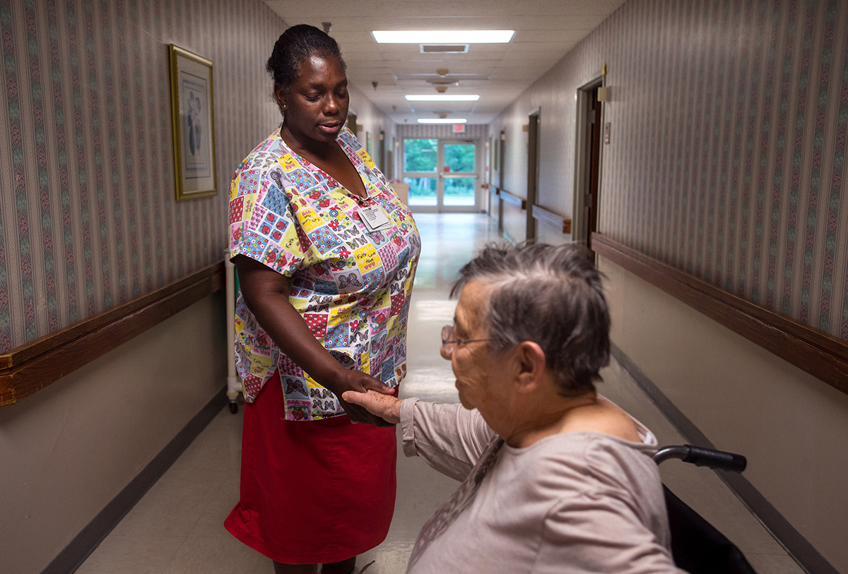 """Ruby shakes hands with a resident at The Carrington. """"I know we got to get paid to make ends meet,""""she said.""""But it's not all about money; it's about me going to work and taking care of them."""""""