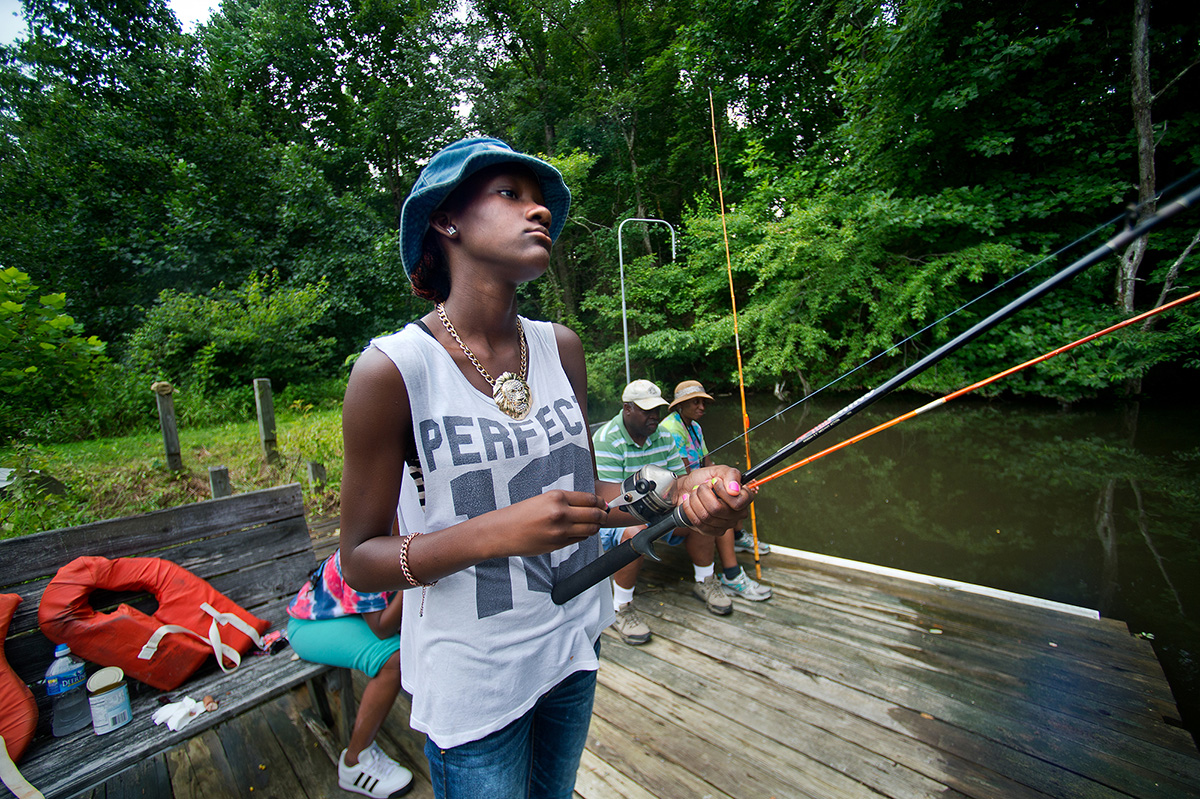 Promise slowly reels in her line as she waits for fish to bite during a fishing trip at a small pond in Bedford, Va. Promise began to express her frustrations after hours of fishing without any luck.