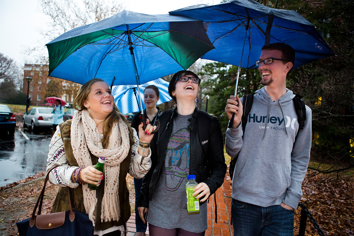 "Natascha Zelloe (left) and Marc Gehlsen (right) combine their umbrellas over Bosch (center) to keep them dry from the rain as they leave their last Chinese class of the semester at the University of Mary Washington. Currently in between majors, Bosch looks to their friends for reinforcement. ""I still don't have all of it figured out, but at least I've got people I can rely on to help get me through things. They've proved themselves to me time and time again, and I couldn't ask for a better support system,"" Bosch said."