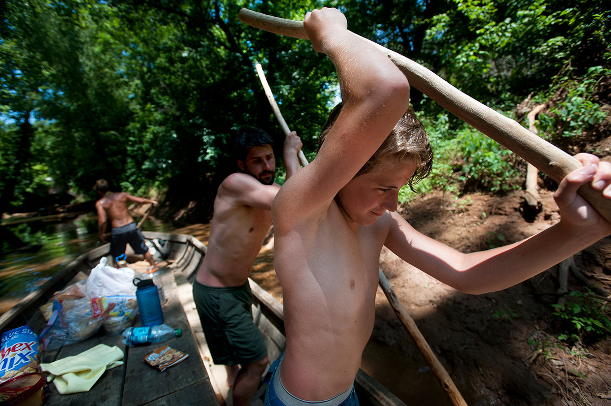 John Morton uses a long wooden pole to help shift the Mary Marshall out of shallow water in a tributary of the James River.