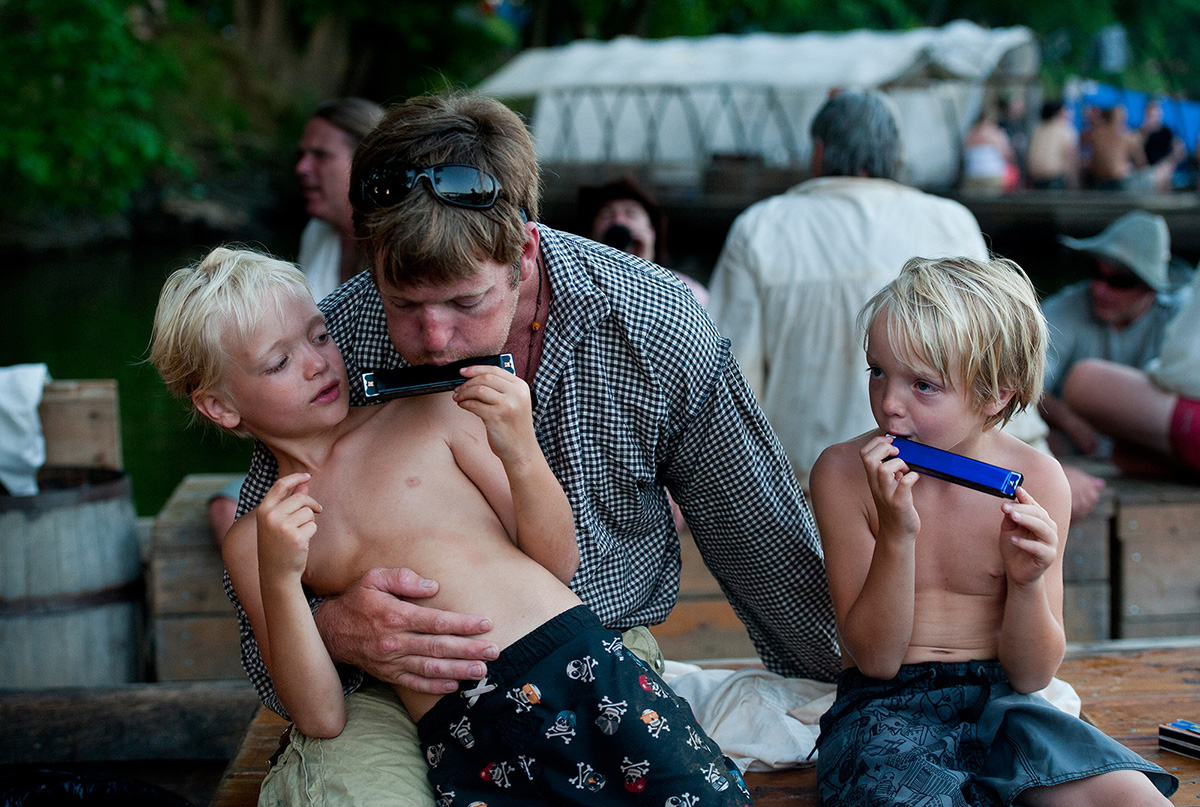 William Davis plays the harmonica with his two sons, Michael, 7, (left) and Ashby (5) after arriving in Scottsville, Va.