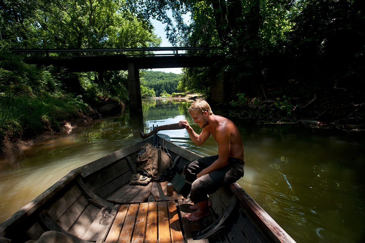 Sebastian Backström helps navigate the Mary Marshall out of a tributary of the James River by managing the sweep as they head towards Scottsville, Va. during the James River Batteau Festival.