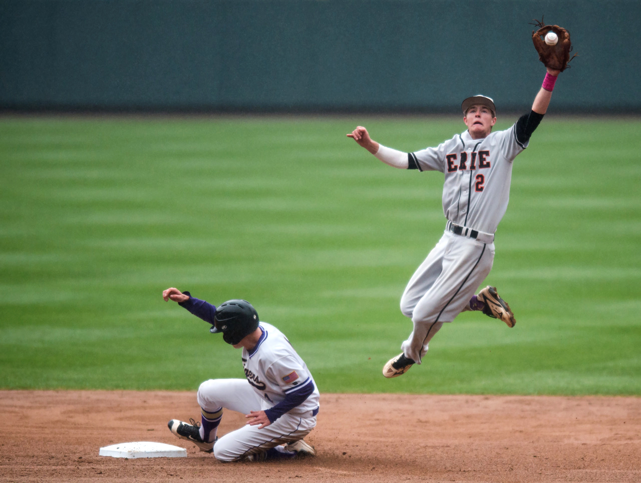 Erie's Josh Crites leaps for the ball as Holy Family's Wayne Rode slides into second base during the game at Coors Field in Denver, Colo.