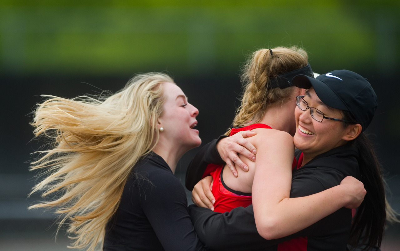 Fairview High School's Natalie Munson (left) and Angela Cai (right) hug Sophie Pearson after Pearson defeated Cherry Creek's Sayuri Garud in a 6-3 victory, winning the state title for their team during the 5A State Tennis Championship Tournament at Gates Tennis Center in Denver, Colo.