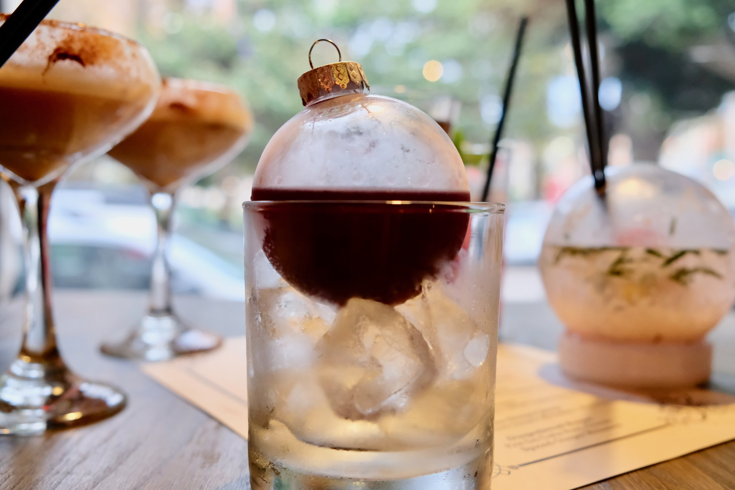 Negroni style drink  served in an ornament // Photo Credit: The Buttery Existence / Cherlyn