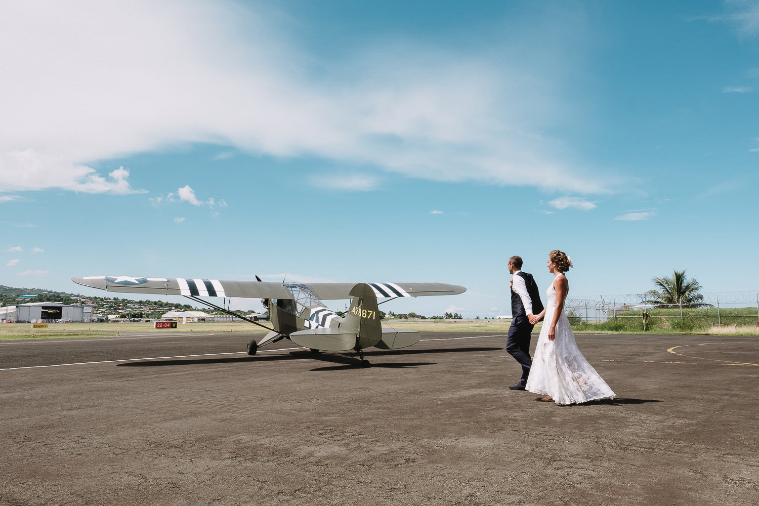 Bride and grrom walking out on to runway with antique plane in t