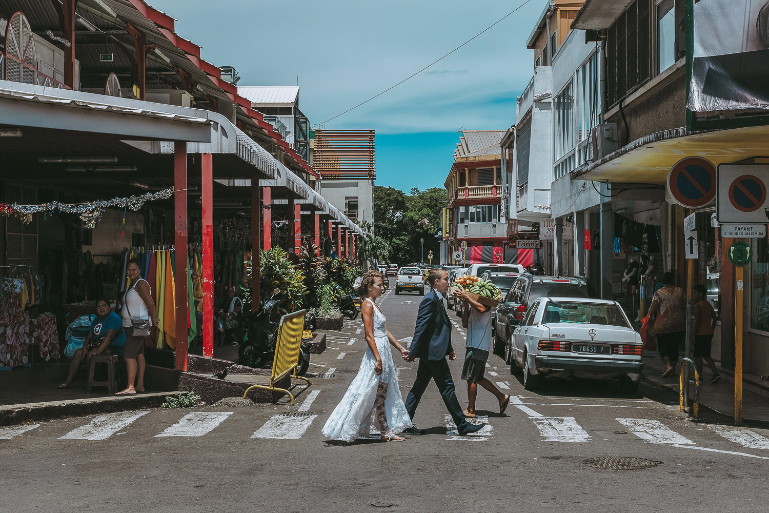 bride and groom walking over zebra crossing at tahiti markets