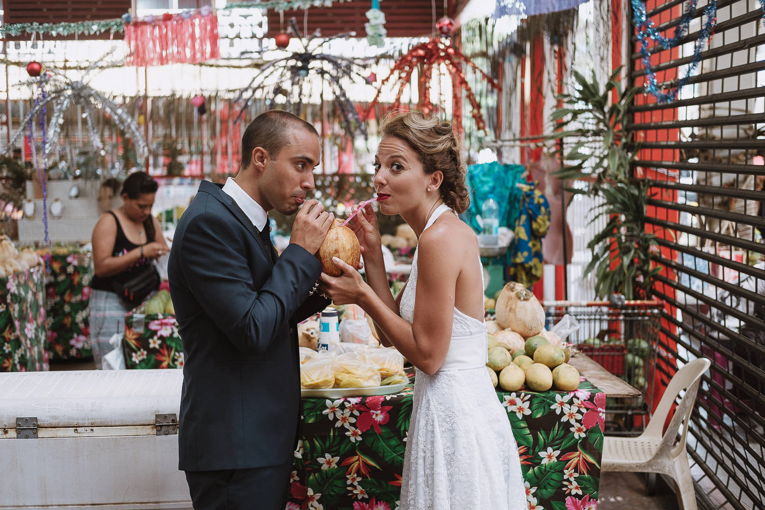 bride and groom sharing a drink from a coconut at tahiti markets