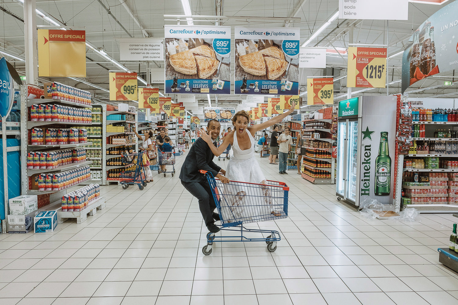 groom pushing bride around in trolley at carrefour tahiti
