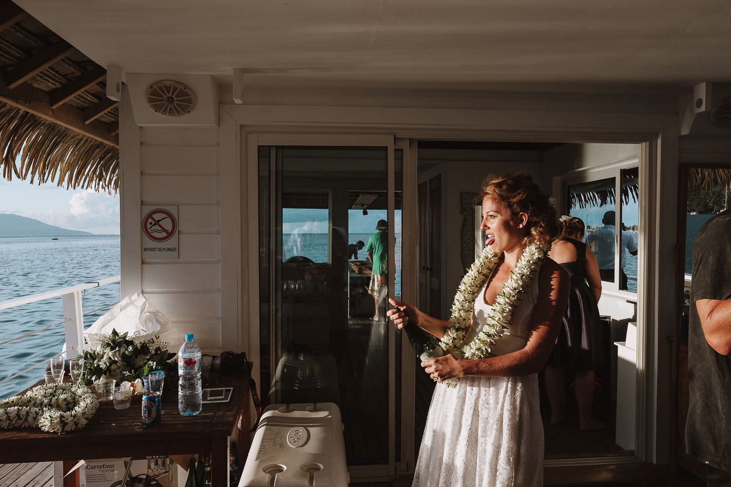 bride popping a champagne bottle on a houseboat in the laggon at