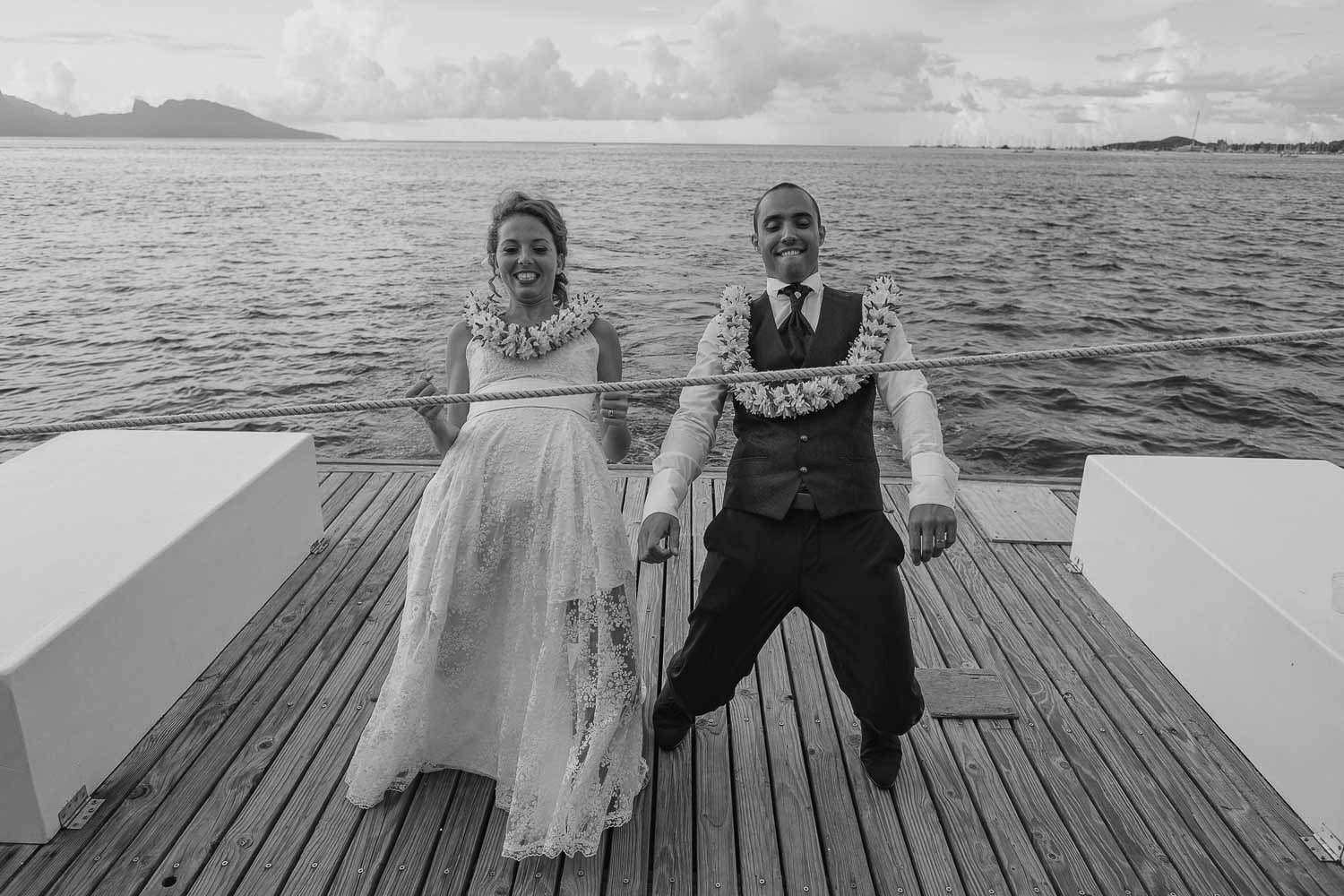 bride and groom doing the limbo on a houseboat in tahiti