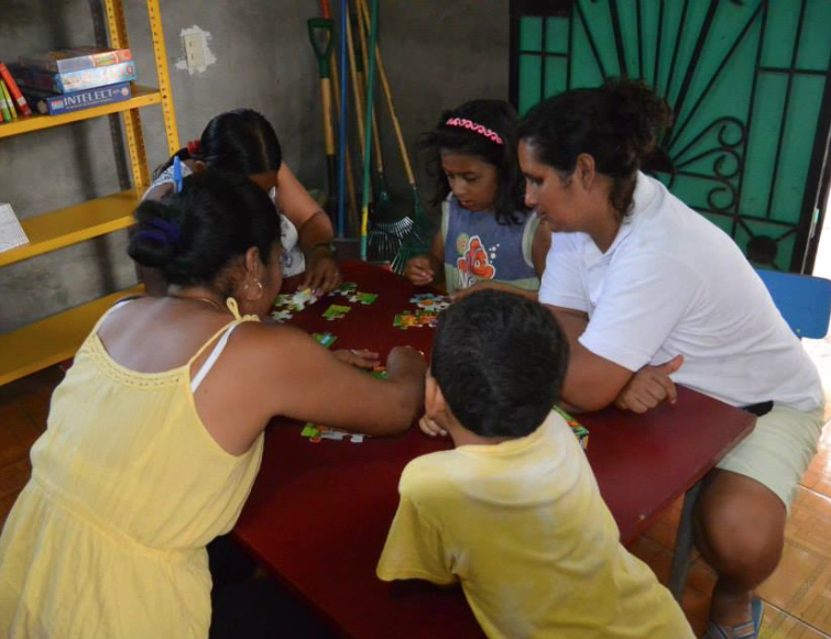 Moms and Kids enjoying jigsaw puzzles at the Mns. Romero Community Library created by Izote