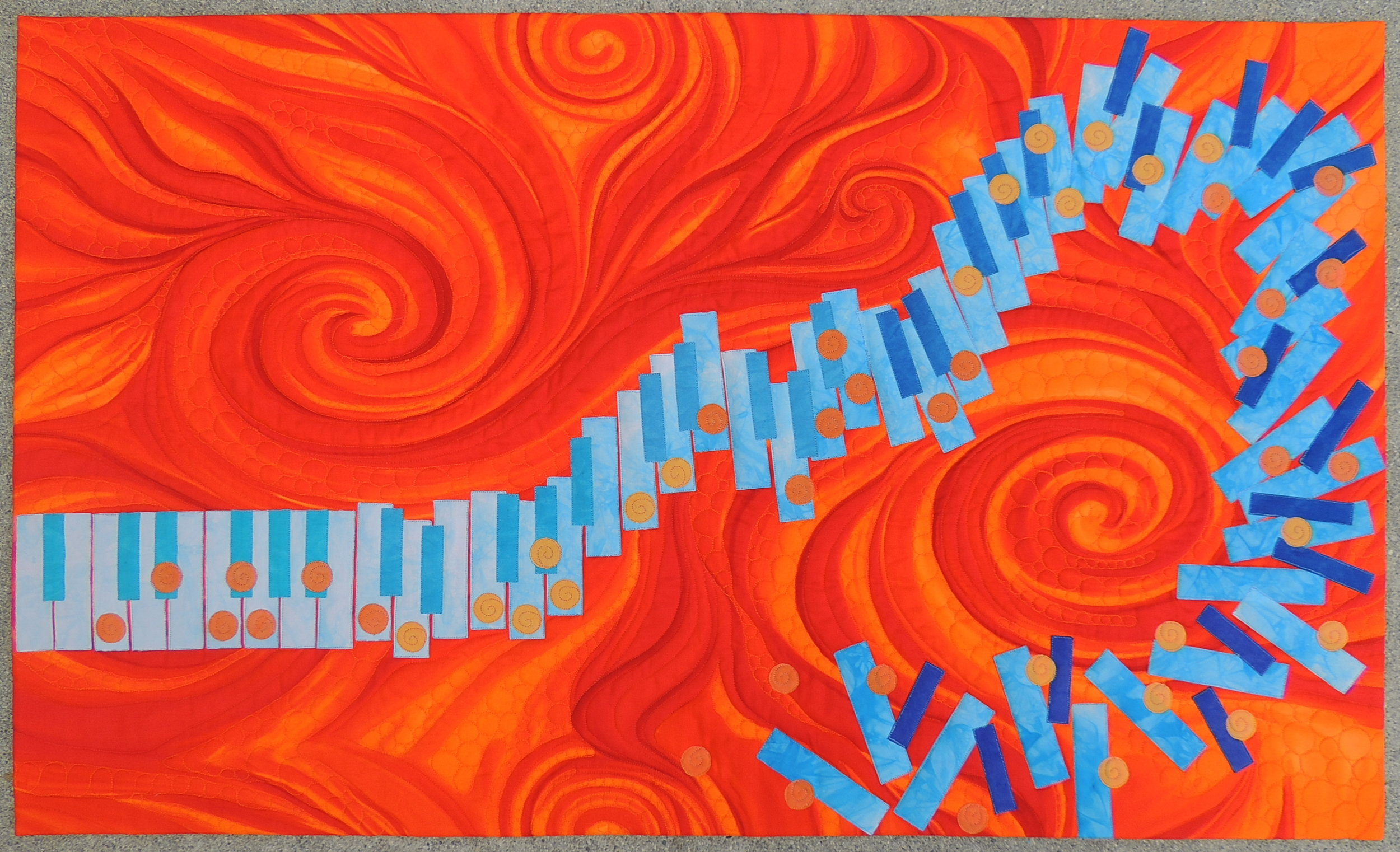 "7. Orange You Glad I Got the Blues?  April 2016 40"" x 24"" Original applique design using hand dyed fabrics and a commercial print to simulate the improvisational nature of Jazz Music.  Exhibits/Awards: Juried into International Quilt Festival (November 2018), 2nd Place in California State Fair in the Art Quilts Small Category (July 2017), won Honorable Mention Ribbon at Pacific International Quilt Festival (October 2016), juried into Jazz Impressions Exhibit at the San Jose Museum of Quilts & Textiles (May 2016).   Blog Post"