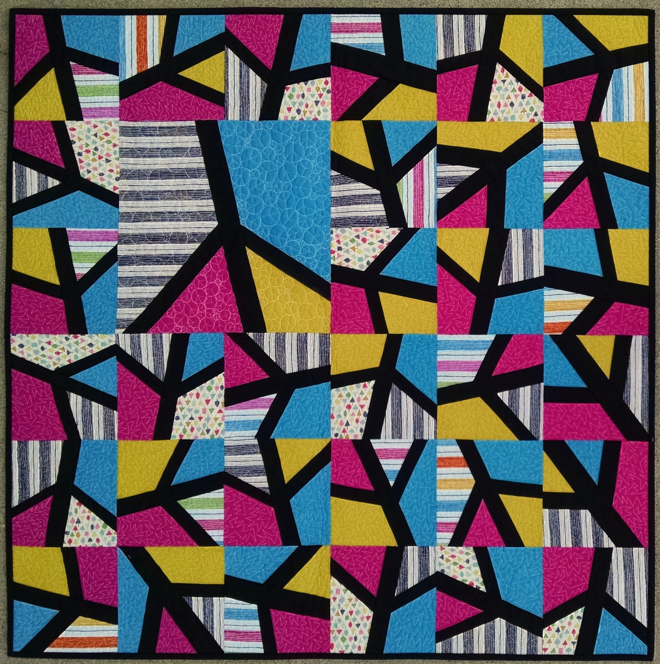 "4. Peace by Piece  November 2017 37"" x 37"" Abstract peace signs dance throughout this improvisationally pieced design. Squares of hyper-bright primary colors were stacked, whacked and shuffled prior to inserting the black strips, creating a modern twist on Mondrian's abstract style featuring a primary palette. Zig zag meander quilting adds energy throughout the smaller blocks, with peace sign filled pebble quilting showcased in the larger peace sign block.  Exhibits/Awards: Juried into Pacific International Quilt Festival New Modern Quilts Competition (October 2018), awarded 3rd Place for Modern Quilts, Small at California State Fair (July 2018), juried into Modern Quilt Guild's QuiltCon (February 2018)   Blog Post"