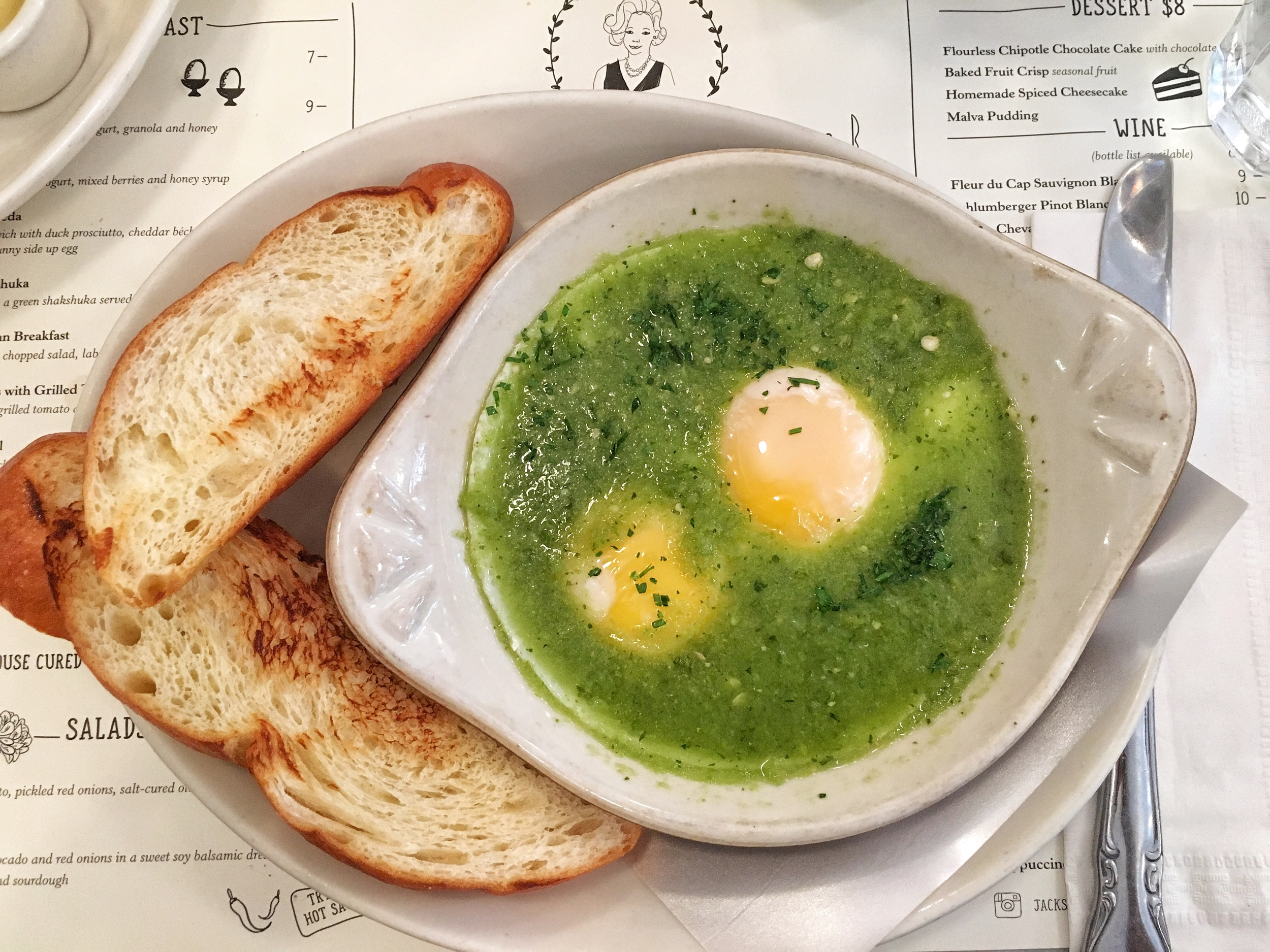 Green shakshuka with two poached eggs and challah bread