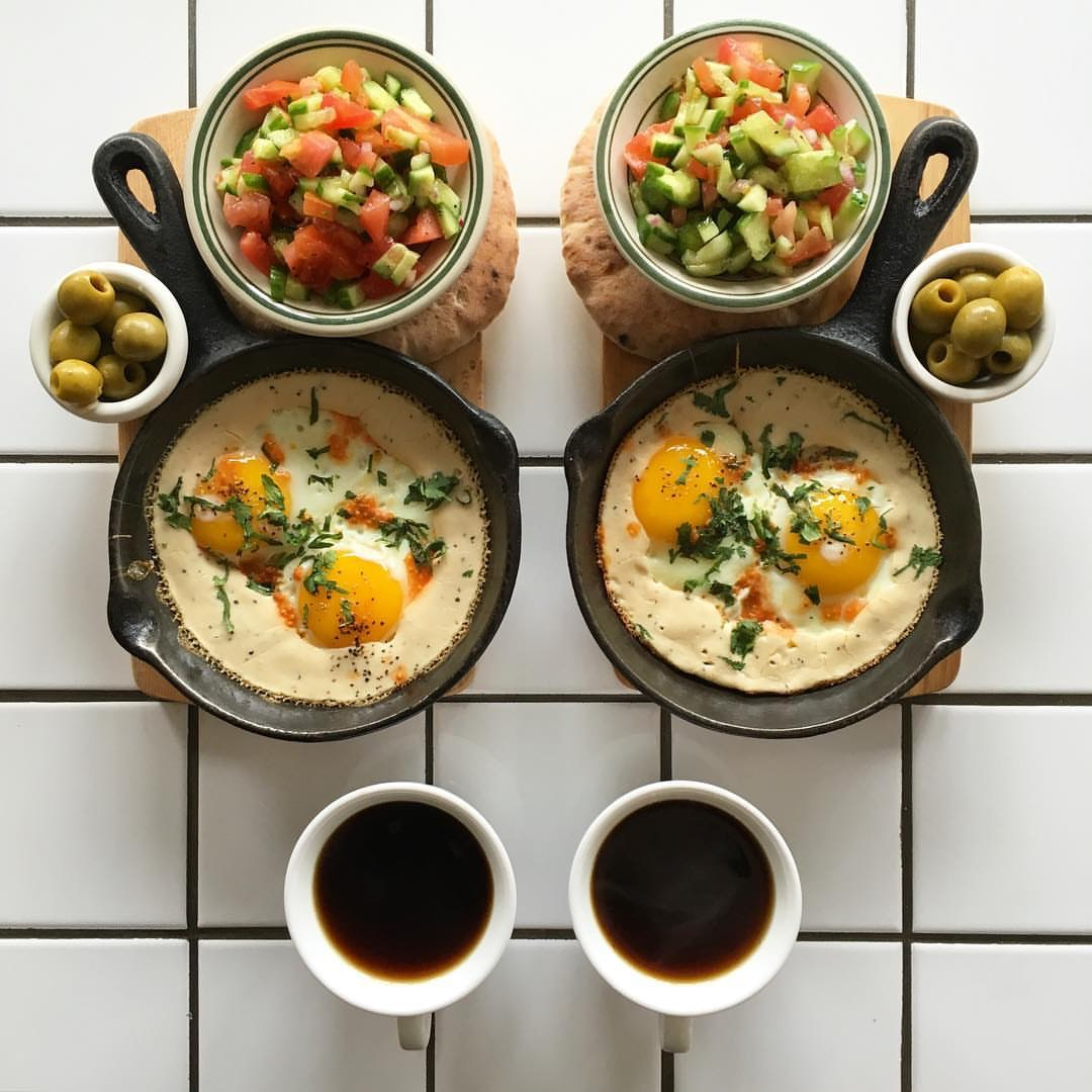 Eggs siniya (eggs cooked in tahini and chilli) with pita, Israeli salad, olives and black coffee. PC: @symmetrybreakfast