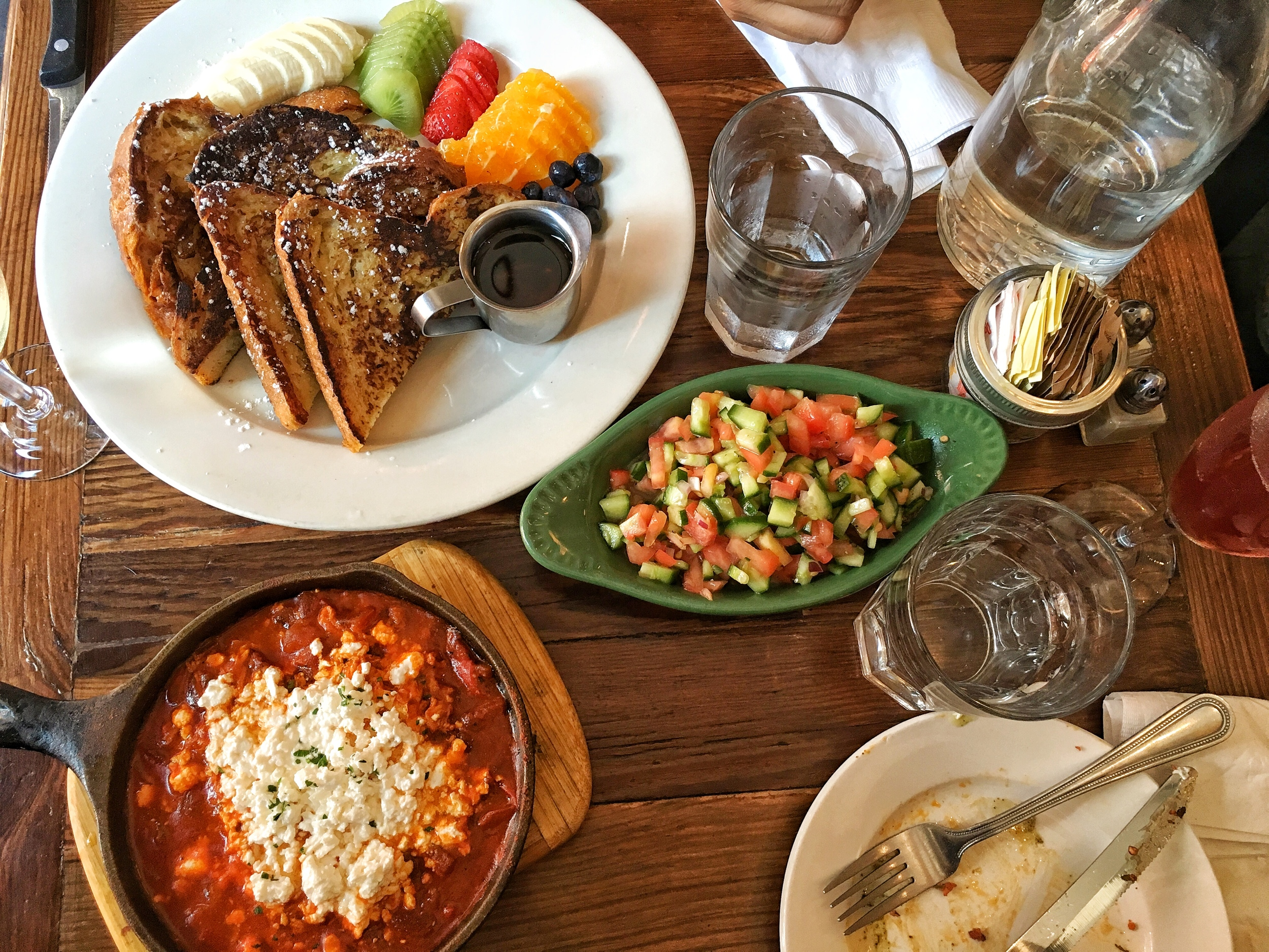 Shakshuka with two baked eggs and feta cheese, Israeli salad, Challah bread french toast with selection of fruits
