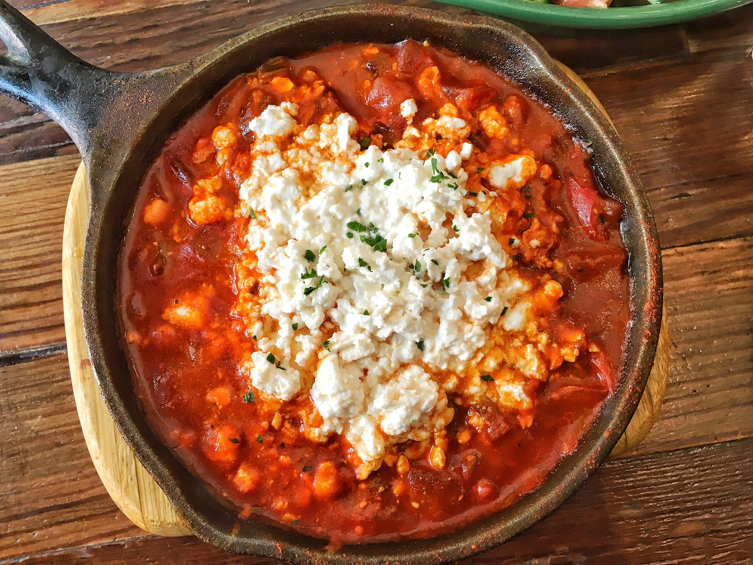 Close up of the 2 egg shakshuka with feta cheese in a spicy Moroccan tomato sauce