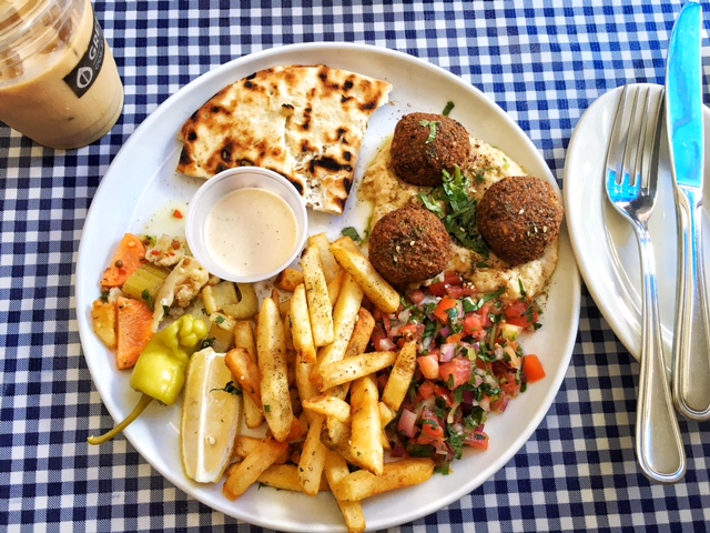 Falafel platter with fries, hummus, tomato salad, pickled vegetables, pita and tzatziki sauce