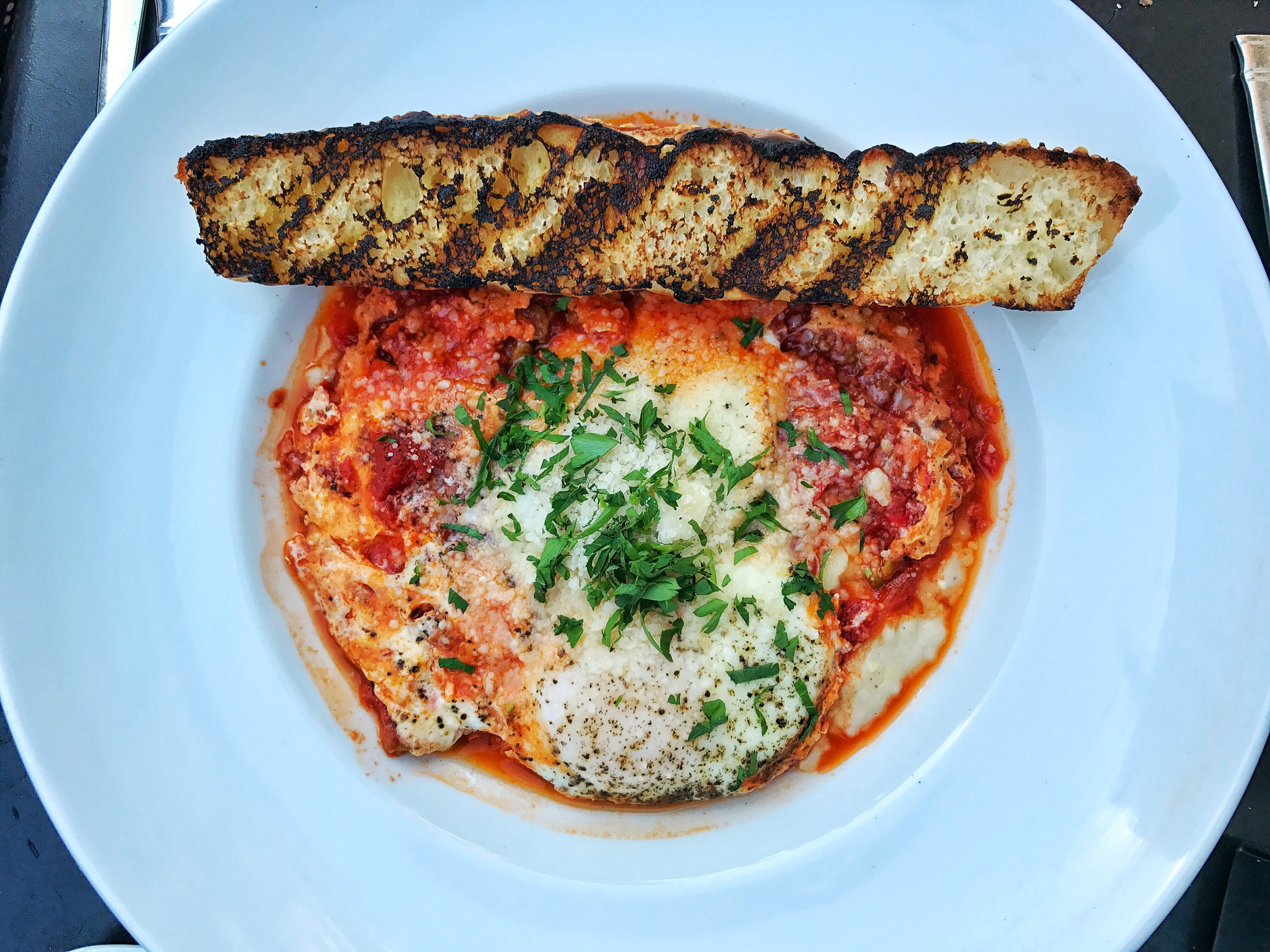 Eggs in purgatory- goat cheese grits, tomato olive ragu, baked eggs and focaccia